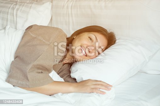 happy woman in beige bathrobe sleeps in soft bed with blanket hugging pillows and opens eyes woken up in hotel room