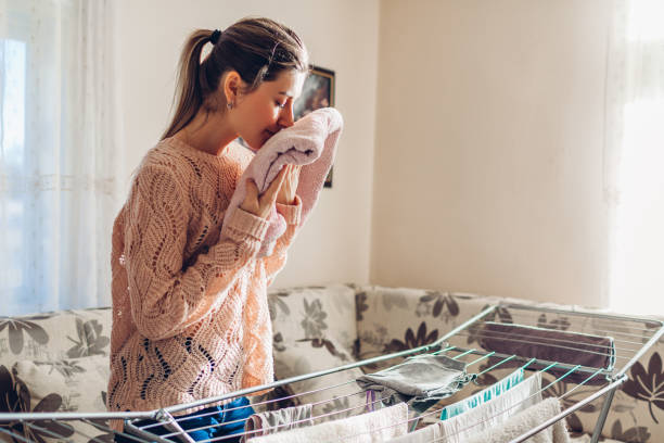 Happy woman smelling gathered clean clothes from dryer in heap. Housekeeping and household chores Happy woman smelling gathered clean clothes from dryer in heap at home. Housekeeping and household chores wet clothing women t shirt stock pictures, royalty-free photos & images