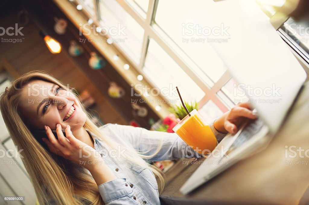 Happy woman smiling and talking with someone on the phone stock photo