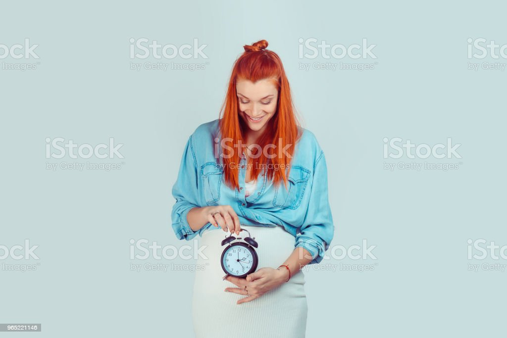 Happy woman smiling holding a clock at big pregnant belly zbiór zdjęć royalty-free