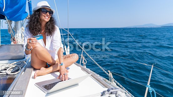 Middle age woman on a yacht in the sea. Happy woman smiling online shoping