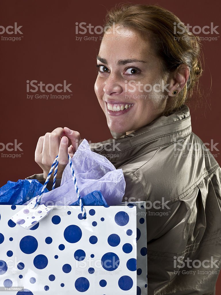 Happy woman smiling over her shoulder, holding gift bags. royalty-free stock photo
