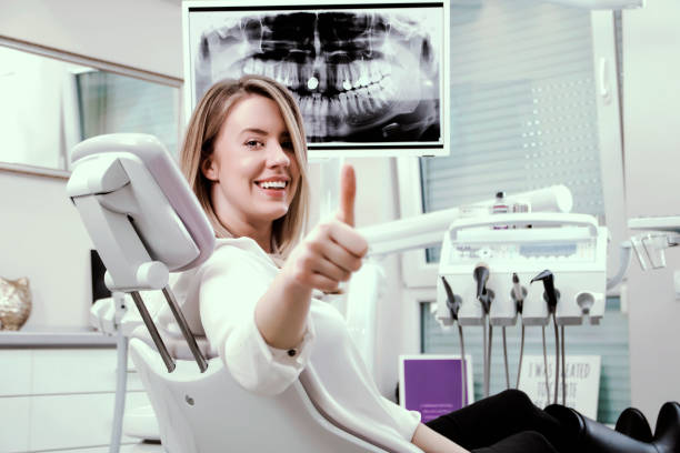 Happy woman smiling showing thumbs up sitting at the dentist office stock photo