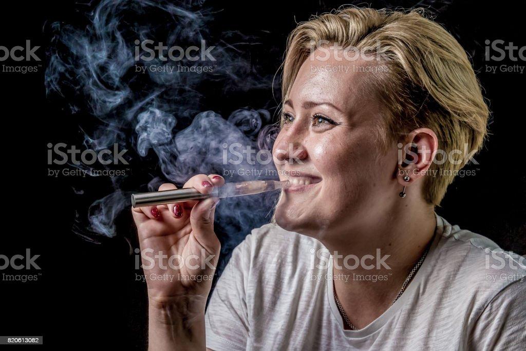Happy woman smoking vaporizer stock photo