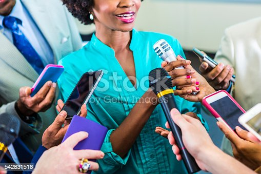 Smiling african american woman speaks to the media. She holds a microphone as she speaks. Other microphones and phones are pointed at her.
