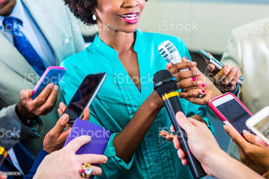 Happy woman speaks to media stock photo