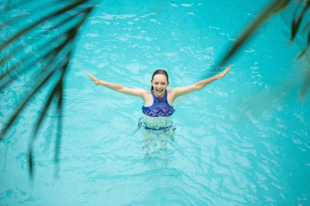 Happy woman splashing in swimming pool stock photo