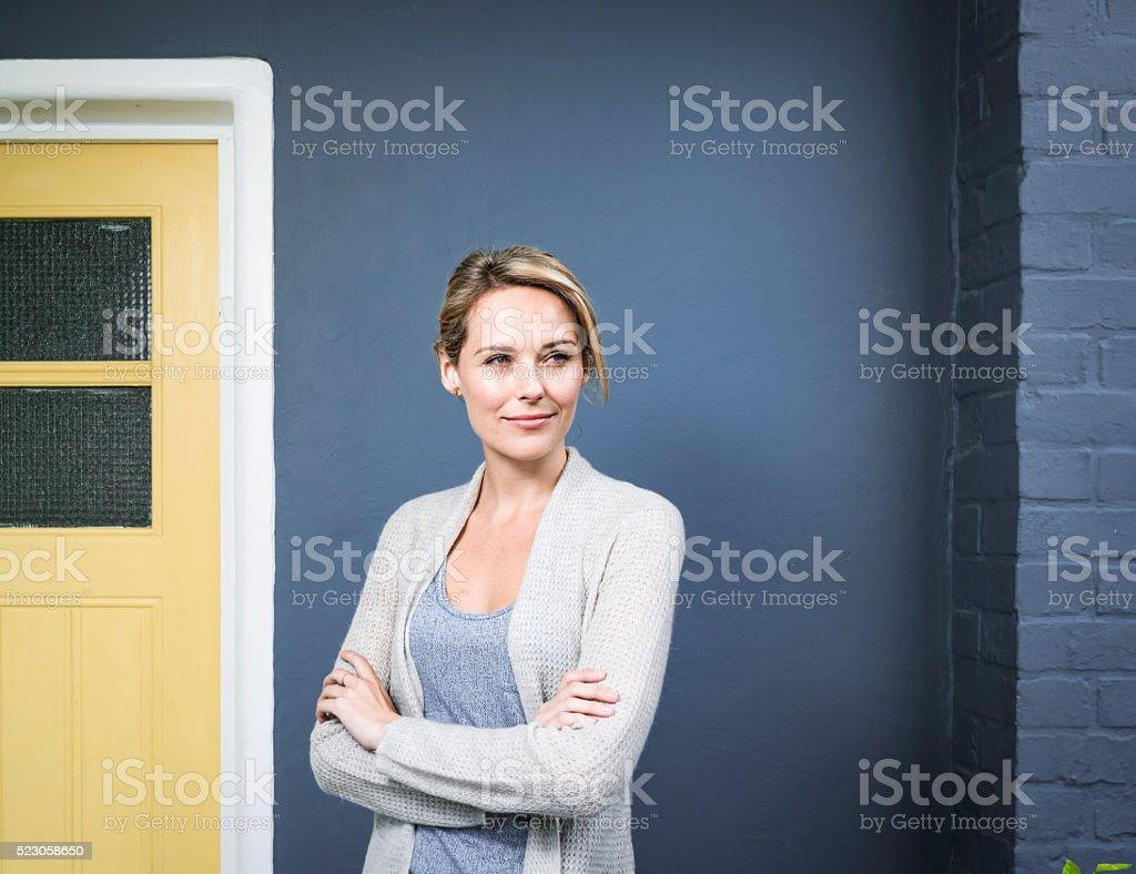 Heureuse femme debout bras croisés en dehors de la maison - Photo
