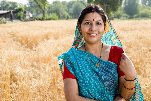 Happy woman standing in agricultural field stock photo