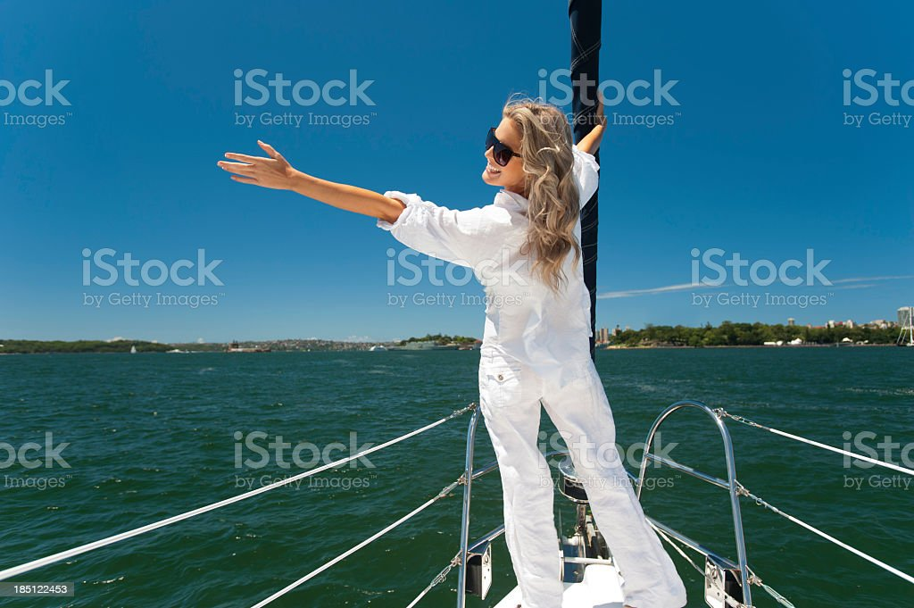 Happy woman standing on the bow of a boat royalty-free stock photo