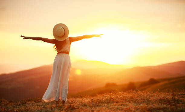 Glückliche Frau steht mit dem Rücken auf Sonnenuntergang in der Natur imit offenen Händen – Foto