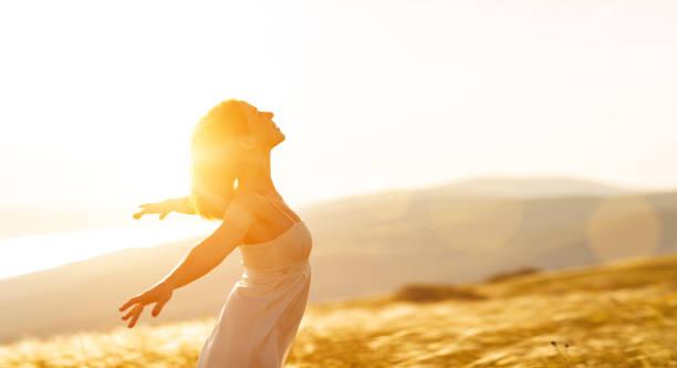 Mulher feliz que está de costas na sunset em mãos abertas de amostra de natureza - foto de acervo