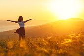 istock Happy woman standing with her back on sunset in nature iwith open hands 835981638