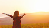 istock Happy woman standing with her back on sunset in nature iwith open hands 838117902