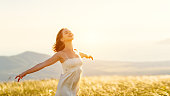 istock Happy woman standing with her back on sunset in nature iwith open hands 839842430