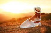 istock Happy woman standing with her back on sunset in nature 1168998463