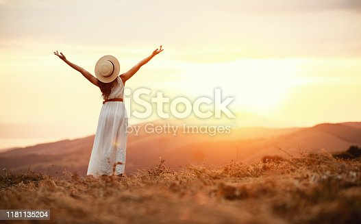Happy woman standing with her back on the sunset in nature in summer