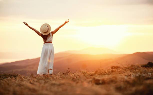 Glückliche Frau steht mit dem Rücken auf Sonnenuntergang in der Natur – Foto