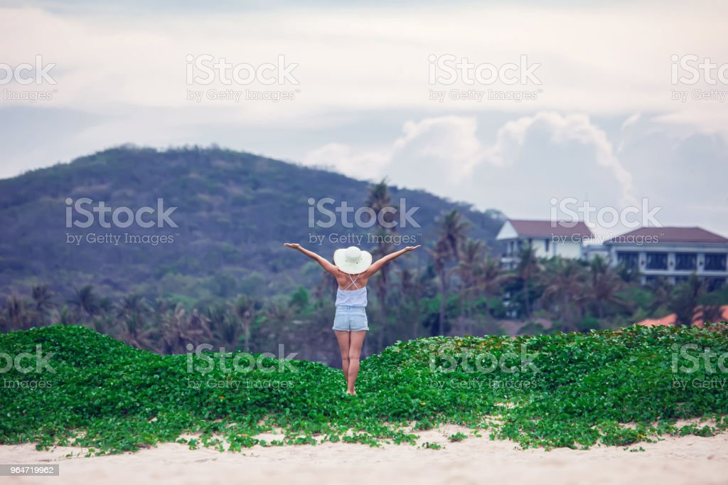 Happy woman stands with raised hands on background of sunset in mountain royalty-free stock photo