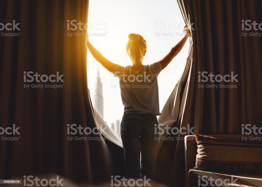 happy woman stretches and  opens curtains at window in morning happy woman stretches and opens the curtains at window in morning Adult Stock Photo