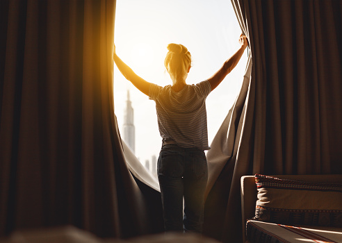 Happy Woman Stretches And Opens Curtains At Window In Morning Stock Photo - Download Image Now