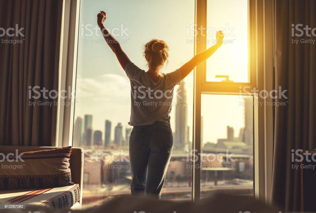 행복 한 여자 뻗어와 아침에 창이에 커튼을 엽니다. royalty-free 스톡 사진