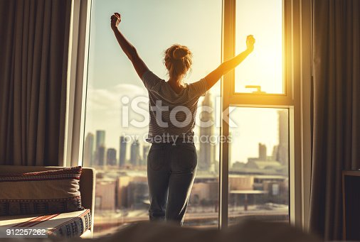 istock happy woman stretches and  opens curtains at window in morning 912257262