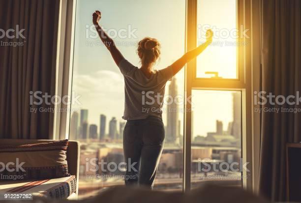 Happy woman stretches and opens curtains at window in morning picture id912257262?b=1&k=6&m=912257262&s=612x612&h=mvicwkeygnjf1cysn uyzdpy5s5jggth7k iknphu i=