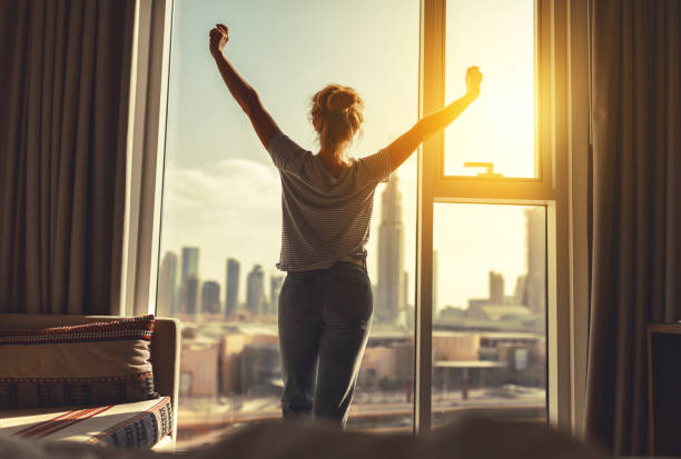 happy woman stretches and  opens curtains at window in morning stock photo