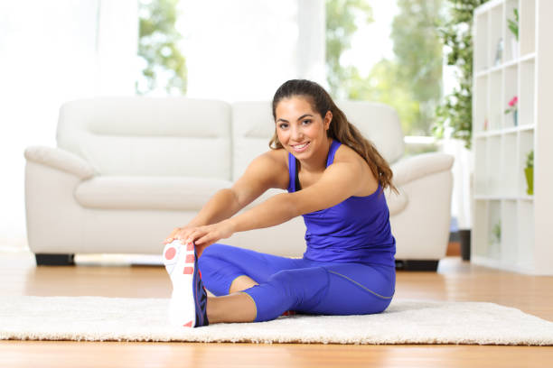 Happy woman stretching after exercise at home Happy woman stretching sitting on the floor after exercise at home hamstring stock pictures, royalty-free photos & images