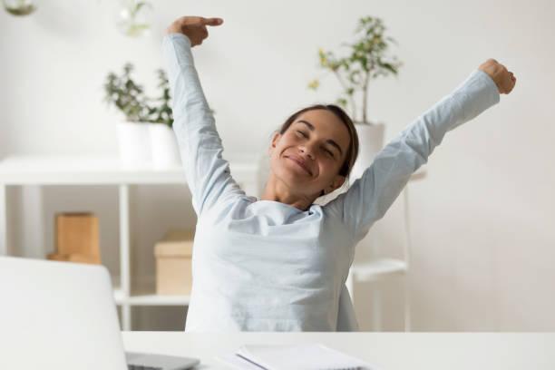 仕事で机の前に伸びる幸せな女性 - 女性会社員 ストックフォトと画像