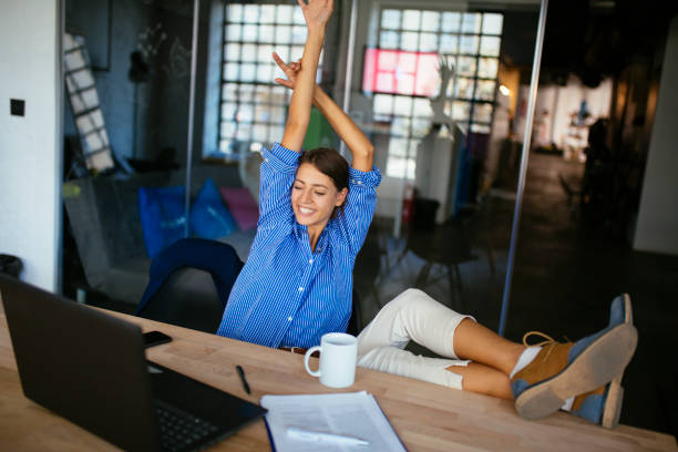 Happy woman stretching in front of desk at work stock photo