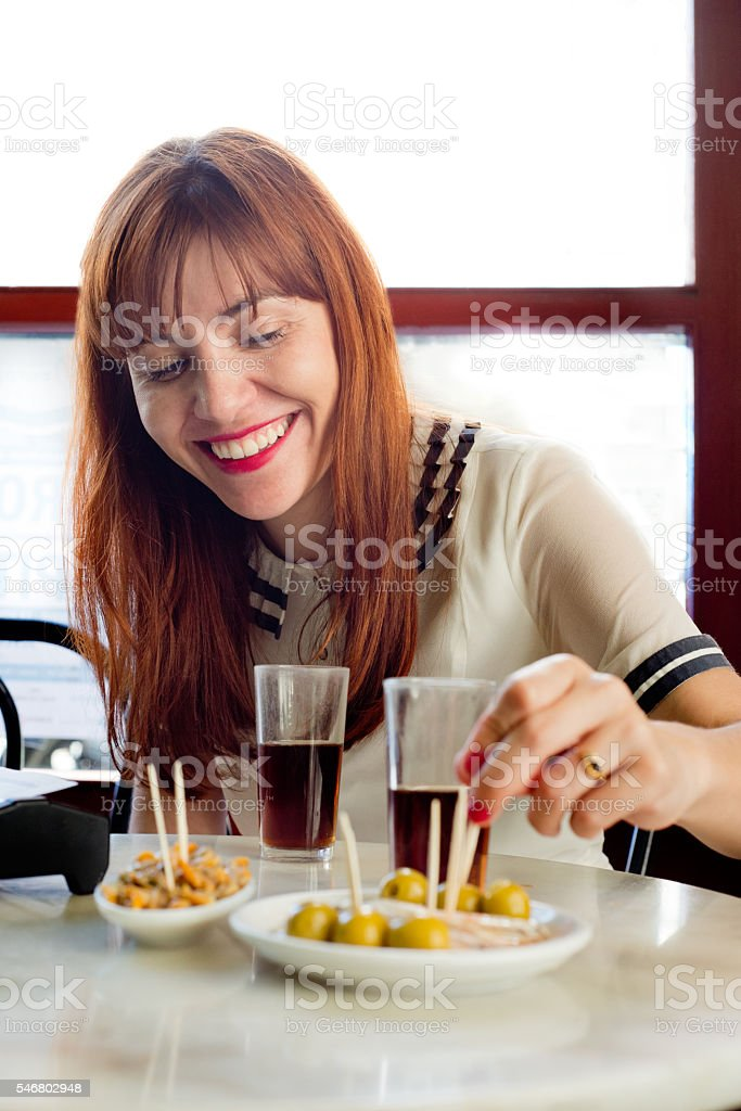 happy woman take spanish vermouth stock photo