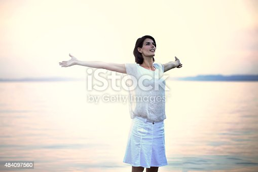 973962328 istock photo happy woman taking a deep breath at the sunset 484097560