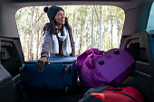 African woman loading bags into the car trunk. Smiling young woman packing / unpacking luggage from the car trunk. View from inside out of the car.