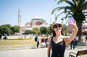 Happy woman taking a selfie in front of Aya Sofya