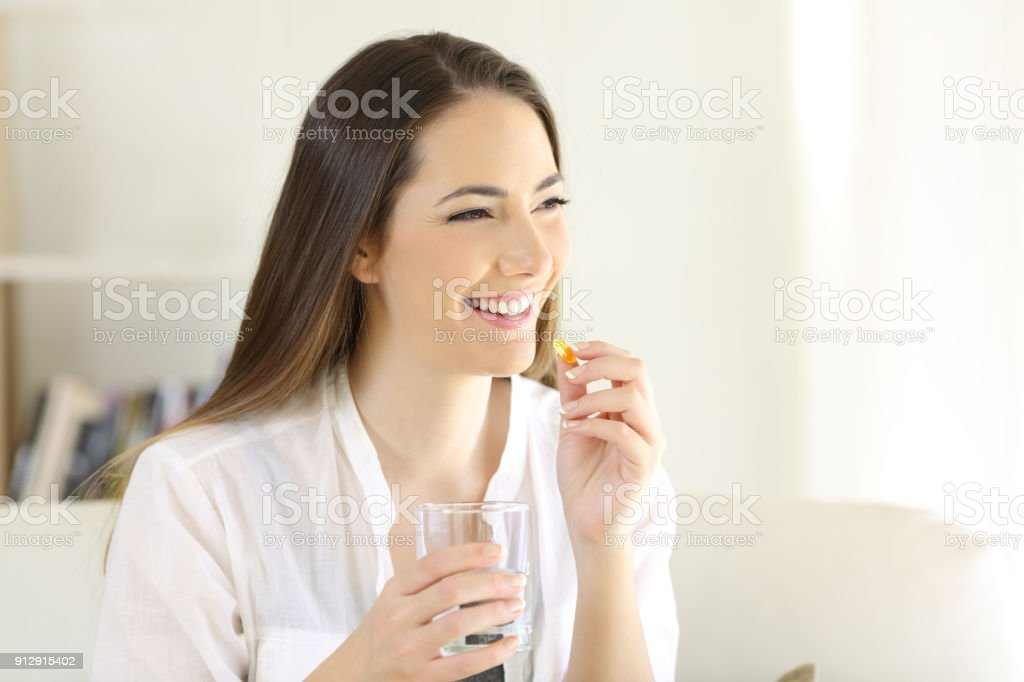 Happy woman taking a vitamin yellow pill at home stock photo
