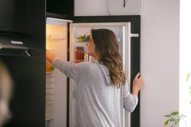 Happy woman taking food from the fridge stock photo