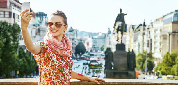 happy woman taking selfie with cellphone in Prague The spirit of old Europe in Prague. happy young woman on Vaclavske namesti in Prague, Czech Republic with cellphone taking selfie wenceslas square stock pictures, royalty-free photos & images