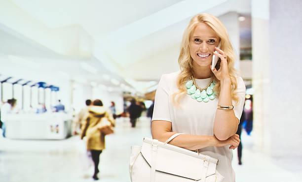 glückliche frau spricht am telefon im einkaufszentrum - canda armband stock-fotos und bilder