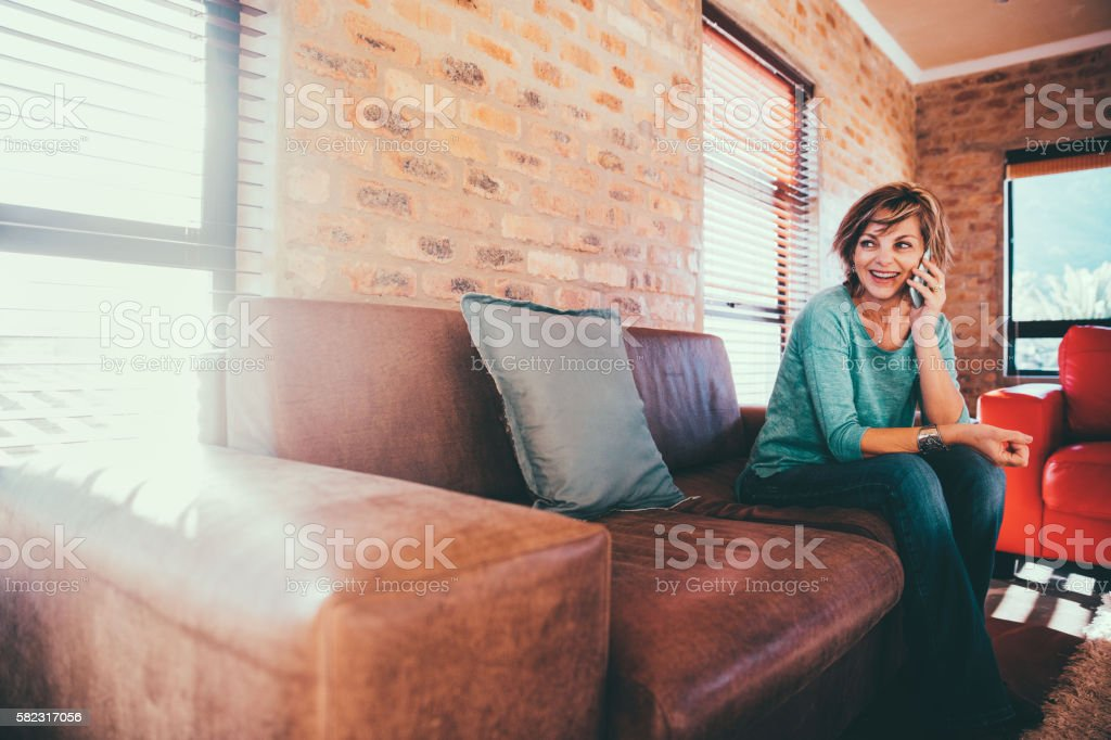 Happy woman talking to her daughter on her smartphone sitting stock photo