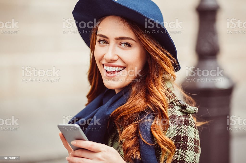 Happy woman text messaging at the street stock photo