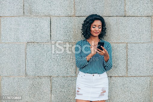 616898108istockphoto Happy woman text messaging through mobile phone 1176720853