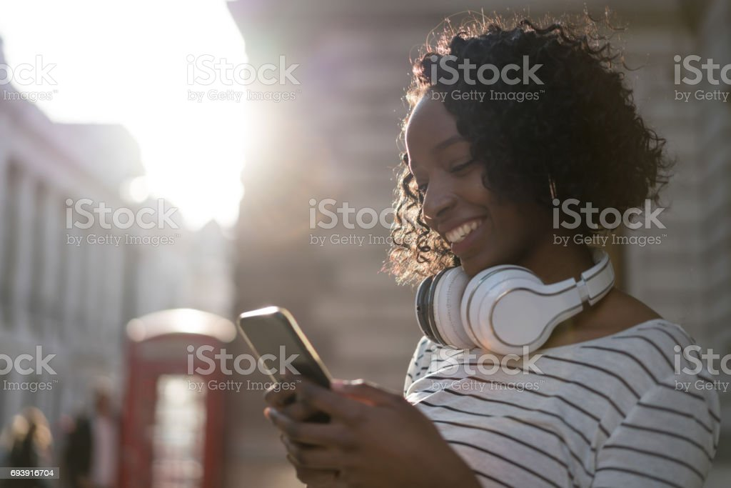 Happy woman texting on her mobile phone stock photo