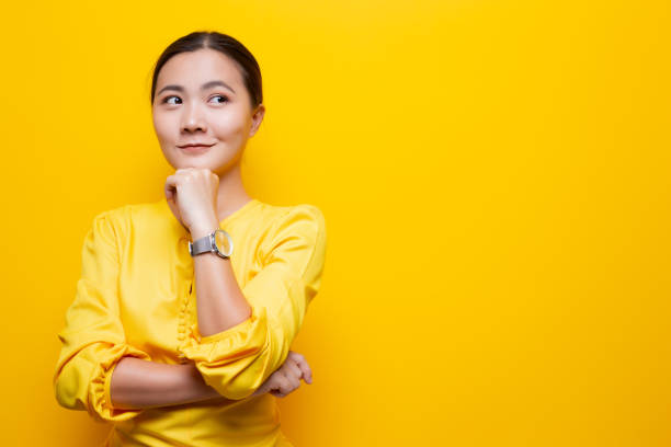 Happy woman thinking and standing isolated over yellow background stock photo