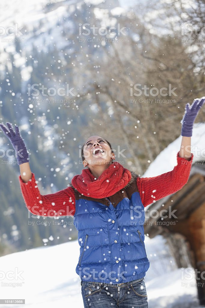 Happy woman throwing snow and looking up royalty-free stock photo