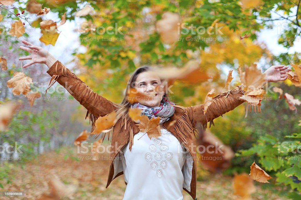 Happy woman throws  leaves royalty-free stock photo