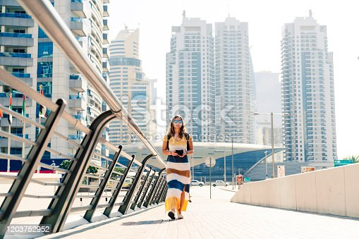 Woman tourist exploring parts of Dubai. Walking around Dubai marina in a long dress covering her legs.