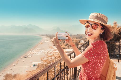 Happy woman travel blogger takes quality photos of the seacoast and Konyaalti beach in Antalya, Turkey