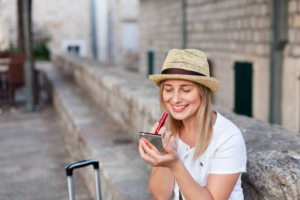 Happy woman traveler corrects makeup with red lipstick outside. Girl tourist with luggage is smiling at town street in Europe. Concept of travel, summer vacation, female tourism, trip, adventure. stock photo